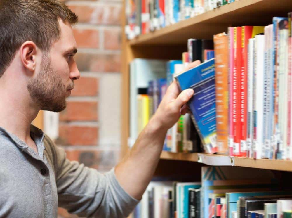 Student taking out a college textbook from a shelf